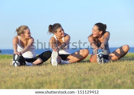 Group of three women stretching after sport on the grass with the sea in the background             - stock photo
