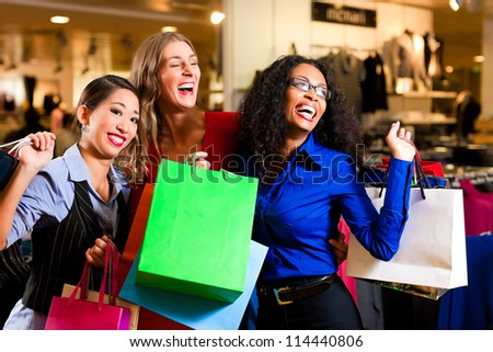 Group of three women - white, black and Asian - shopping downtown in a mall - stock photo