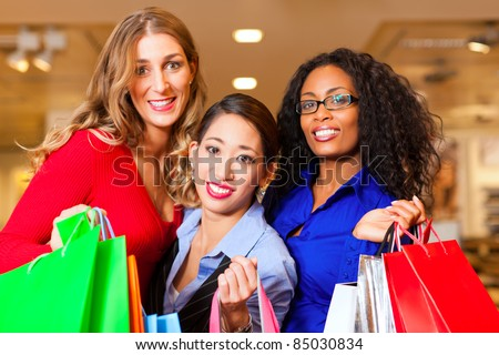 Group of three women - white, black and Asian - shopping downtown in a mall with Christmas decoration