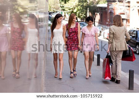 Group of three young beautiful women looking after a hansome man with many shopping bags walking on the street.