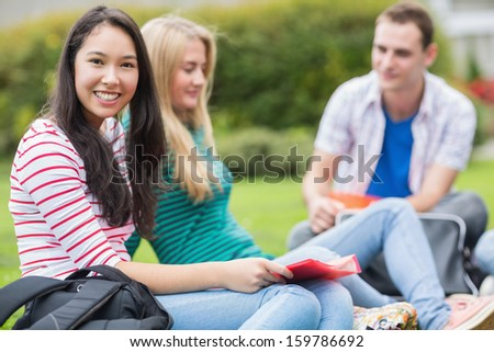 Group of three young college students sitting in the park