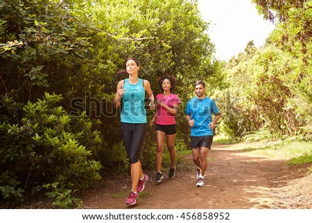 Group of three young joggers running a natural trail in daylight surrounded by trees and bushes in the late morning wearing t-shirts and black pants