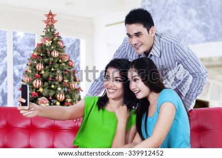 Group of three young people sitting on the sofa while taking selfie photo using cellphone, shot with a christmas tree background on the window - stock photo