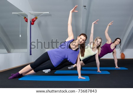 Group of three young women doing exercises in a fitness club - stock photo