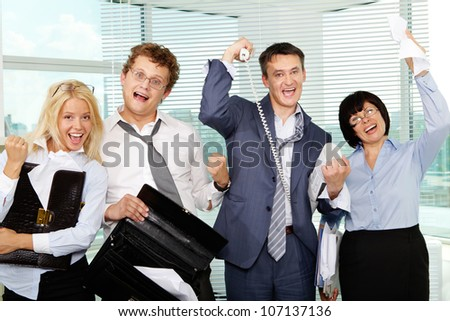 Group of tired businesspeople showing gladness after making excellent deal