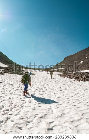 Group of tourists climbing mountain pass each other in the snow, rear view - stock photo