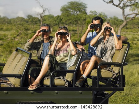Group of tourists sitting in jeep and looking through binoculars - stock photo