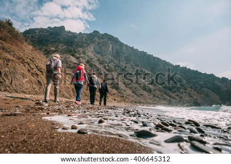 Group of tourists walking on the shingle beach of Crimea on a sunny day with backpacks