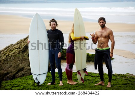 Group of tree professional surfers standing on the beach, blonde california girl, sexy muscular brunette man and red hair handsome man, summer holidays on surf camp - stock photo
