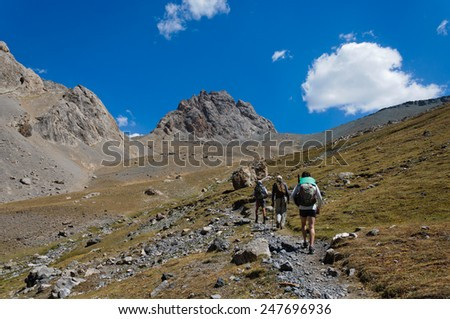Group of trekkers in the Fany mountain against the blue sky with clouds - stock photo