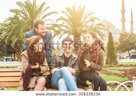 Group of Turkish friends in Istanbul. They are two men and two women, sitting on a bench at park with a mosque on background. They are wearing warm clothes. Travel and lifestyle concepts. - stock photo