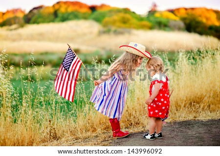 group of two happy adorable little kid girls smiling and waving American flag outside, his dress with strip and stars, cowboy hat. Smiling child celebrating 4th july - Independence Day - stock photo