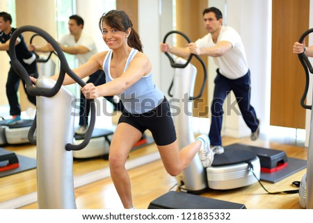 Group of two men and one woman on a vibration massage plate in a gym - stock photo
