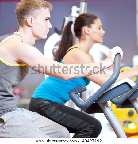 Group of two people in the gym, exercising their legs doing cardio cycling training