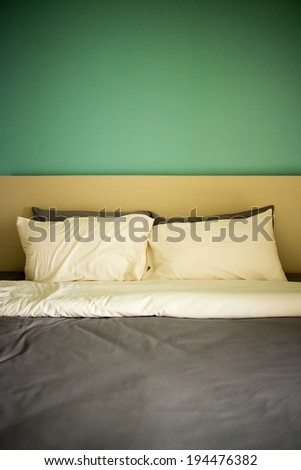 Group of two white pillows on a bed with headboard. - stock photo