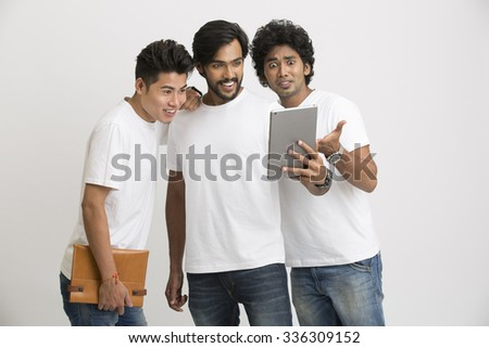 group of university friends surprisingly looking at pc tablet on white background.   - stock photo