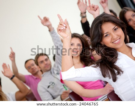 Group of university students in a classroom rising their hands - stock photo