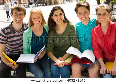 Group of university students studying, reviewing homework in park - stock photo