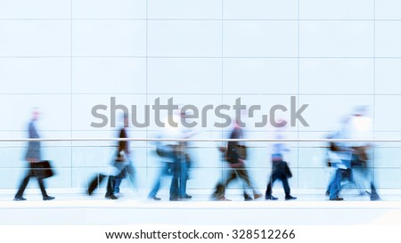 Group of unrecognizable business people in front of a wall, blurred motion, copy space above the people - stock photo