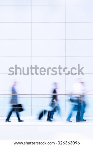 Group of unrecognizable business people in front of modern architecture, blurred motion  - stock photo