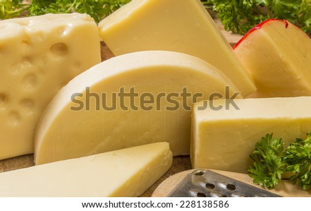 """group of various cheese's ready to enjoy or cook with asiago,swiss,gouda,provolone,gruyere,chedder. """"cheese"""" - stock photo"""