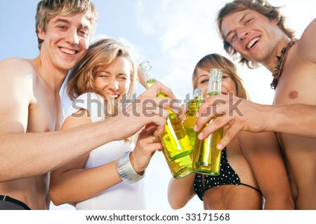 Group of very beautiful people celebrating on the beach in the summer of their lives - focus on bottles - stock photo