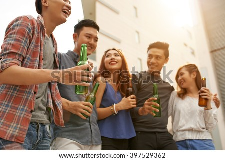 Group of Vietnamese young people drinking beer and chatting outdoors
