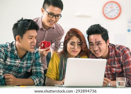 Group of Vietnamese young people gathered in front of laptop - stock photo