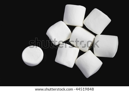Group of white marshmallows on black background - stock photo