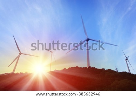 Group of windmills on top of mountain, against sunrise background.
