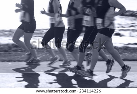 Group of woman compete in the race on coastal road. Blurred motion. Monochromatic - stock photo