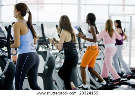 group of women at the gym doing exercise on the xtrainer machines - stock photo