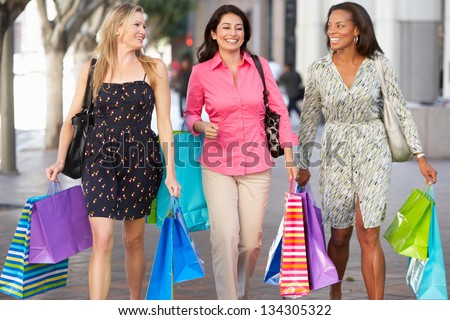Group Of Women Carrying Shopping Bags On City Street - stock photo