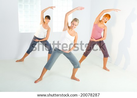 Group of women doing fitness exercise. They're looking at camera. Front view. - stock photo