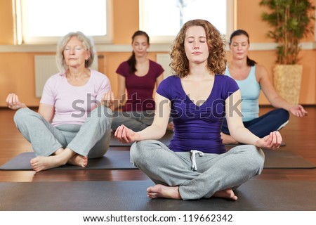Group of women doing relaxing yoga exercises in gym