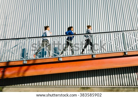 Group of women running on a ramp. Urban outdoor training people. - stock photo