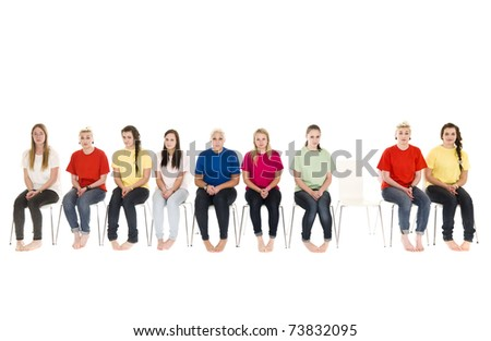 Group of women sitting on chairs and one empty chair - stock photo