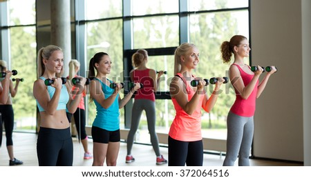 group of women with dumbbells in gym - stock photo