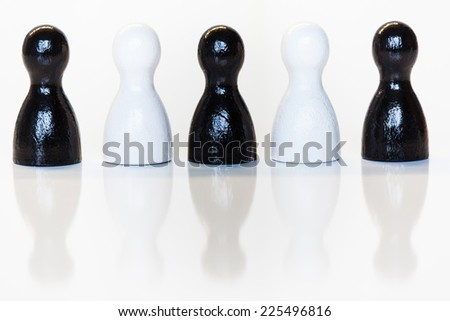 Group of wooden toy figurines, black and white, with reflection on bottom. Diversity, ethnicity or racial issues concept. - stock photo