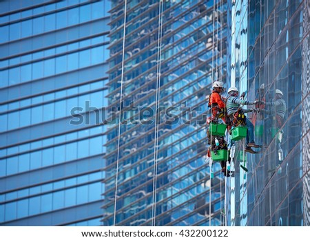 Group of workers cleaning windows at Singapore skyscraper - stock photo