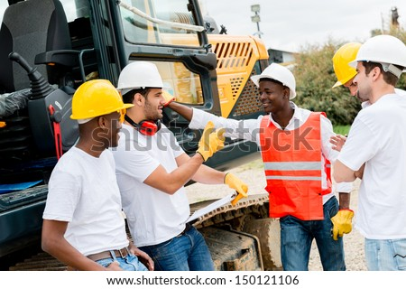 Group of workers talking at a building site  - stock photo