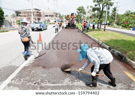 Group of workers working on Asphalt paving with Para Slurry Seal Truck on road renovation - stock photo