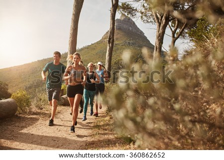 Group of young adults training and running together through trails on the hillside outdoors in nature. Fit young people trail running on a mountain path. - stock photo