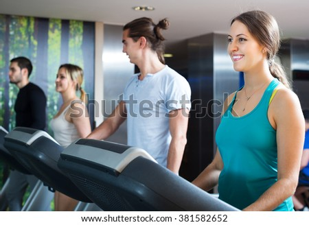 Group of young adults training on treadmills in gym - stock photo