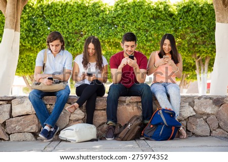 Group of young adults using their smartphones at school