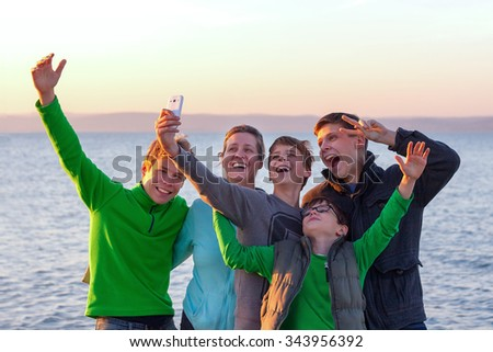 Group of young and happy people mostly boys with an adult woman taking a selfie (selfi) with a lake in the background - stock photo