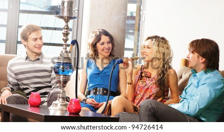 Group of young and sexy people smoking hookah in the lounge cafe - stock photo