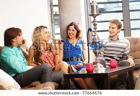 Group of young and sexy people smoking hookah in the lounge caffee - stock photo