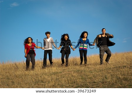 Group of young asian beautiful people running in the meadow - stock photo