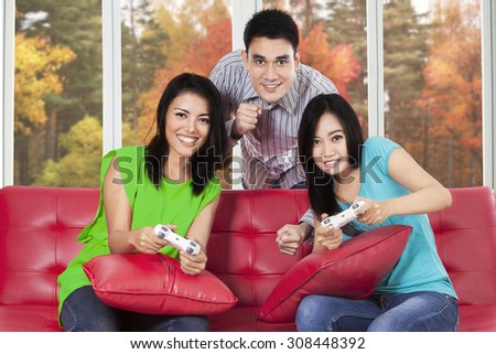 Group of young asian people enjoy an autumn holiday by playing video games together at home - stock photo